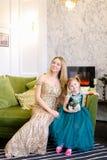 Vestido vestindo da mãe caucasiano nova e da filha pequena que senta-se no sofá na sala de visitas imagem de stock