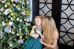 Vestido vestindo da mãe loura nova e da filha pequena que está a árvore de Natal próxima fotografia de stock