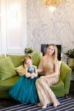 Vestido vestindo da mãe nova e da filha pequena que senta-se no sofá na sala de visitas fotos de stock