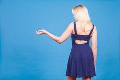 Vestido vestindo da marinha da mulher que aponta à esquerda a mão aberta Imagens de Stock Royalty Free