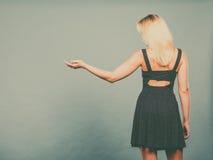 Vestido vestindo da marinha da mulher que aponta à esquerda a mão aberta Imagem de Stock Royalty Free