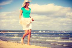 Vestido vestindo da mulher loura que anda na praia Imagem de Stock