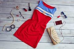 Vestido y accesorios rojos hermosos en un fondo de madera Fotos de archivo