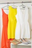 Vestidos coloridos brillantes que cuelgan en la suspensión de capa, los zapatos y handba Imágenes de archivo libres de regalías