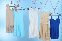Vestidos coloridos que cuelgan en la suspensión de ropa Imagen de archivo libre de regalías
