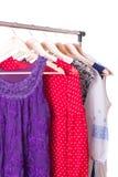 Vestidos de cores diferentes em ganchos de madeira Foto de Stock