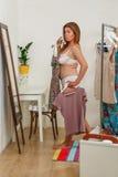Vestidos de tentativa da mulher em casa fotografia de stock