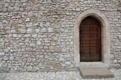 Vesting of kasteelmuur van gestapelde steenblokken wordt gemaakt en een houten deur met gotische stijl gerichte boog die stock foto's