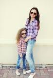 Vestir bonito da mãe e da criança camisas quadriculado e óculos de sol Imagem de Stock