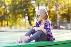 Vestir da criança óculos de sol e camisa quadriculado que sentam-se na cidade Fotografia de Stock Royalty Free