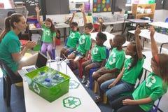 Vestir das crianças da escola recicla o t-shirt que levanta a mão para responder em uma pergunta fotos de stock