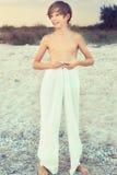 Vestir de sorriso do menino calças brancas largas, estando na costa Fotografia de Stock Royalty Free