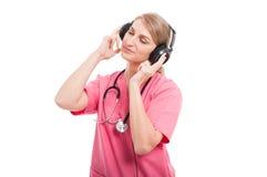 Vestir fêmea da enfermeira esfrega a apreciação da música de escuta Foto de Stock Royalty Free