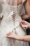 Vestire i vestiti dalla sposa Immagine Stock