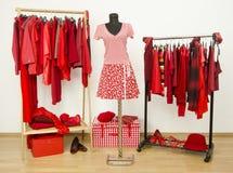 Vestire il gabinetto con i vestiti rossi ha sistemato sui ganci e su un outf Fotografie Stock Libere da Diritti