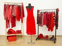 Vestire il gabinetto con i vestiti rossi ha sistemato sui ganci e su un vestito su un manichino Fotografia Stock Libera da Diritti