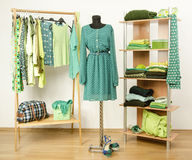 Vestire il gabinetto con i vestiti verdi ha sistemato sui ganci e lo scaffale, si veste su un manichino Fotografie Stock