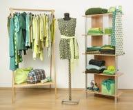 Vestire il gabinetto con i vestiti verdi ha sistemato sui ganci e lo scaffale, si veste su un manichino Immagini Stock