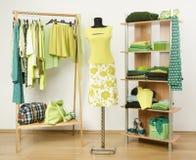Vestire il gabinetto con i vestiti verdi ha sistemato sui ganci e sullo scaffale, attrezzatura verde al neon su un manichino Fotografia Stock