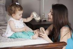 Vestiresi della neonata Fotografia Stock