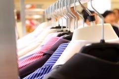 Vestiti appesi in un deposito Fotografie Stock Libere da Diritti