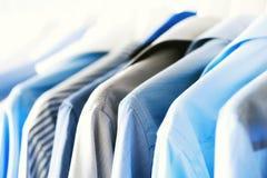 Vestiti blu di colore Vestiti, rivestimenti maschii e camice appendenti sulla ferrovia dei vestiti Copi lo spazio bandiera fotografia stock