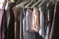 Vestiti casalinghi dei colori differenti che appendono nel deposito Fotografia Stock