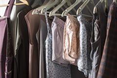 Vestiti casalinghi dei colori differenti che appendono nel deposito Fotografie Stock Libere da Diritti