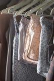 Vestiti casalinghi dei colori differenti che appendono nel deposito Immagini Stock Libere da Diritti
