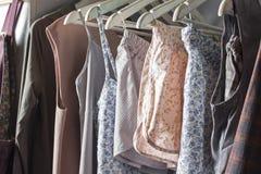 Vestiti casalinghi dei colori differenti che appendono nel deposito Immagini Stock