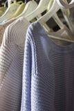 Vestiti casalinghi tricottati dei colori differenti che appendono nello stor Fotografia Stock Libera da Diritti