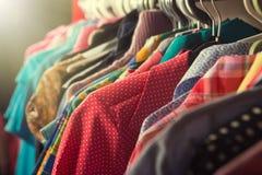 Vestiti che appendono sullo scaffale nel deposito immagini stock libere da diritti