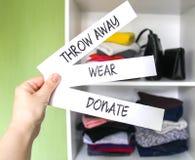 Vestiti che ordinano nel guardaroba domestico per donazione, l'uso e lo scarto Indossi, doni e getti via le note di carta in una  immagini stock