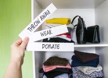 Vestiti che ordinano nel guardaroba domestico per donazione, l'uso e lo scarto Indossi, doni e getti via le note di carta in una  immagine stock libera da diritti