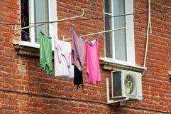Vestiti che si asciugano su una corda sotto una finestra Fotografia Stock Libera da Diritti
