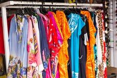 Vestiti Colourful che appendono nel fondo del deposito o del mercato Fotografie Stock