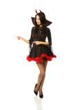 Vestiti d'uso del diavolo della donna che indicano a sinistra Fotografia Stock Libera da Diritti