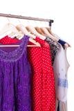 Vestiti dei colori differenti sui ganci di legno Fotografia Stock