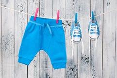 Vestiti del bambino che appendono sulla corda da bucato. immagine stock