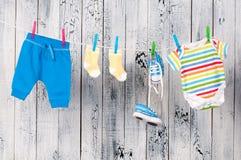 Vestiti del bambino che appendono sulla corda da bucato. Fotografie Stock Libere da Diritti