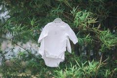 Vestiti del bambino che appendono sulla corda da bucato Immagini Stock