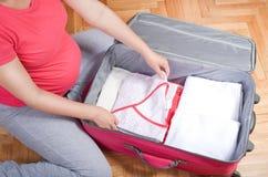 Vestiti del bambino dell'imballaggio della donna incinta Fotografia Stock