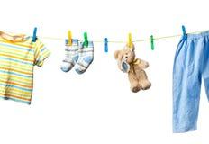 Vestiti del bambino e un orso di orsacchiotto Fotografia Stock