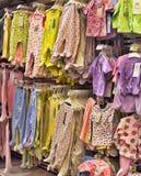 Vestiti del bambino per i neonati nel deposito Immagine Stock