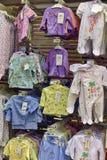 Vestiti del bambino per i neonati nel deposito Fotografie Stock Libere da Diritti