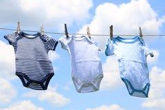 Vestiti del bambino su una linea Immagini Stock