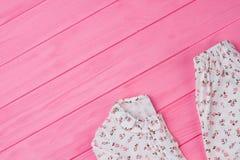 Vestiti del ` delle ragazze sulla tavola rosa Fotografie Stock