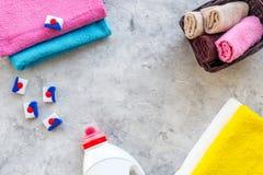 Vestiti del lavaggio Asciugamano pulito e detersivo sul copyspace di pietra grigio di vista superiore del fondo immagine stock libera da diritti
