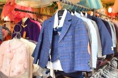 Vestiti del ragazzino che appendono su una gruccia per vestiti immagine stock