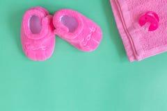 Vestiti del ` s dei bambini e bottini del bambino su fondo verde Fotografie Stock